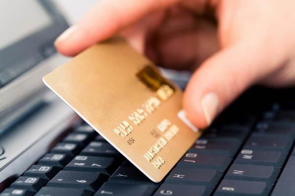 Image of plastic credit cart between human fingers