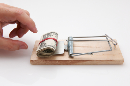Male hand taking rolled up dollar bills from mousetrap
